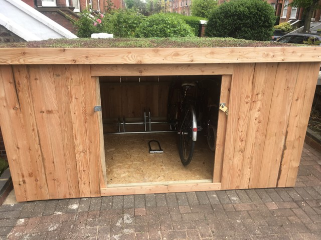 Slot in shed for 6 bikes with living roof and sliding doors .