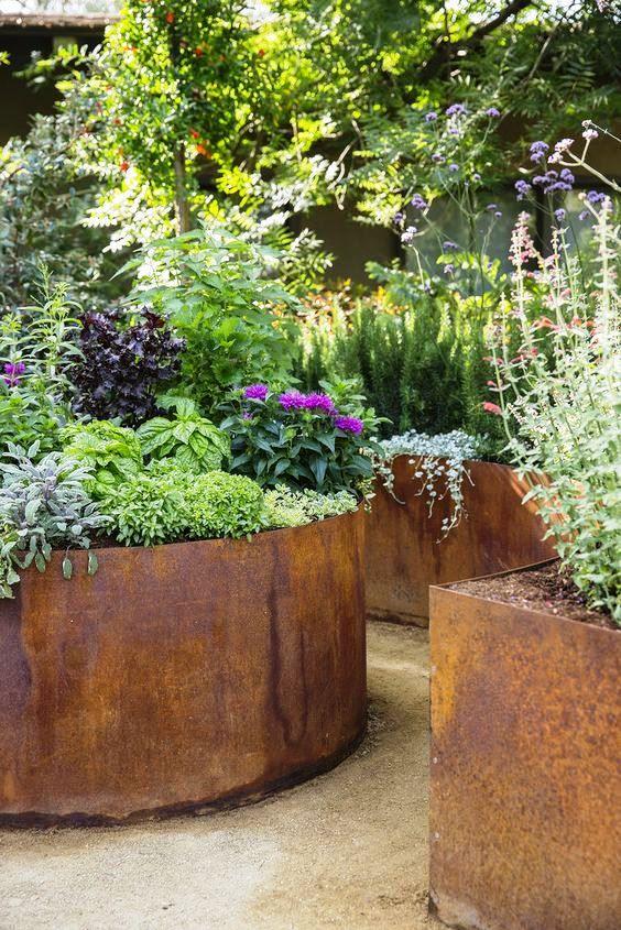 Corten planters look so beautiful in this modern cottage garden .