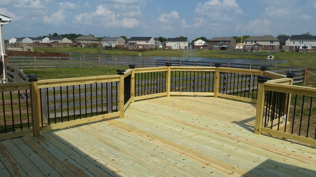 Octagonal wood deck with black aluminum balusters, and solar post .