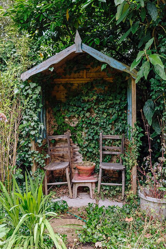 Small garden shelter with two chairs in a rural garden by Paul .