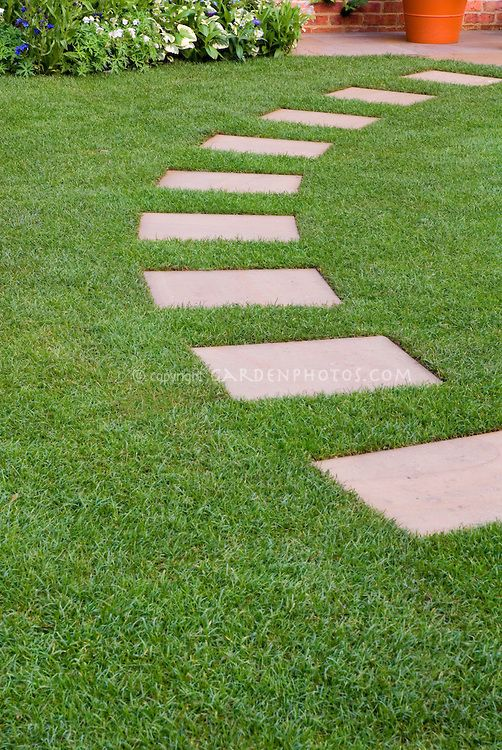 Stepping stones in perfect lawn grass, leading in an arc to .