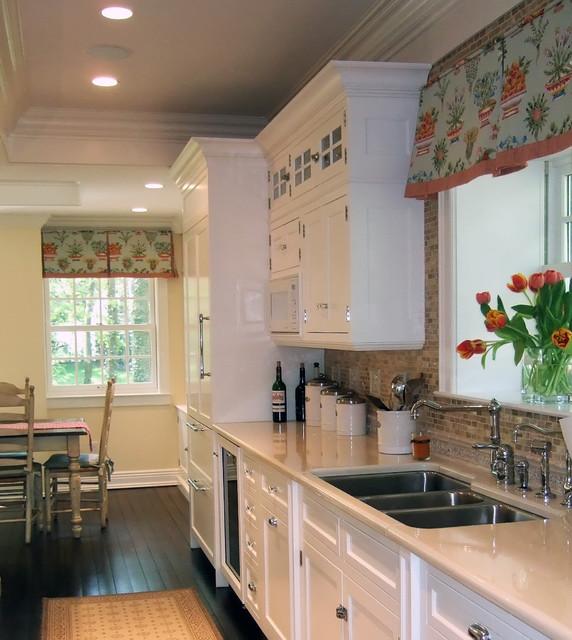 white kitchen dark floors colorful window treatment - Traditional .
